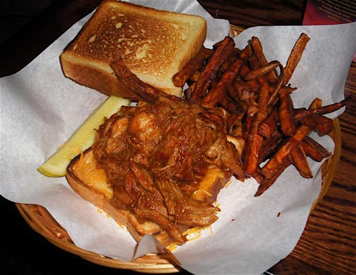 Pulled pork with Carolina-style sauce with Cheddar cheese on Texas toast with red onion relish and sweet potato fries